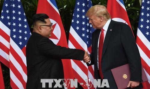 Tổng thống Mỹ Donald Trump (phải) và nhà lãnh đạo Triều Tiên Kim Jong-un (trái) trong cuộc gặp thượng đỉnh tại Singapore ngày 12/6. Ảnh: YONHAP/ TTXVN
