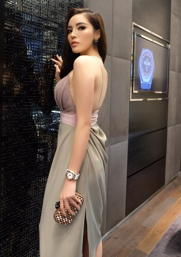 Cô đeo đồng hồ, mang clutch hàng hiệu, tạo dáng kiêu sa trước ống kính.