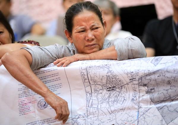 Người dân Thủ Thiêm mang bản đồ quy hoạch đến buổi làm việc. Ảnh: Hữu Khoa.