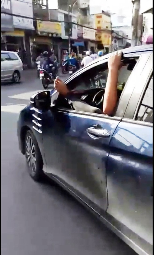 TP HCM: Tài xế gác chân lên cửa ô tô, phóng vun vút trên đường - Ảnh 1.