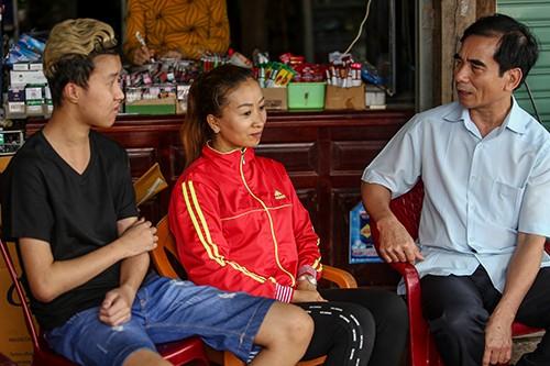 Ông Hiếu (bìa phải) thăm hỏi gia đình chị Thoa - người Việt gặp nạntrong vụ vỡ đập. Ảnh: Tiến Thành.