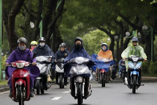 Khoảng 8h30, mưa đã ngớt song nhiều người vẫn mặc áo mưa chống rét.
