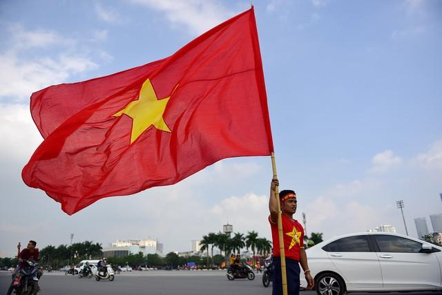 Một cổ động viên chuẩn bị lá cờ Tổ quốc lớn để tham gia diễu hành cùng đoàn.