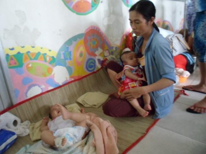 Kiều Nguyên – Kiều Anh, hai bé sinh đôi tám tháng tuổi nằm dưới nền gạch hành lang bệnh viện