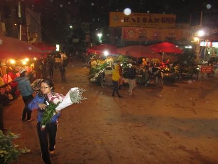 Tất cả các hàng quán ở chợ hoa Tây Hồ đã sáng đèn, người bán mua tấp nập, thậm chí người đến sớm đã mua xong hoa và chuẩn bị ra về.