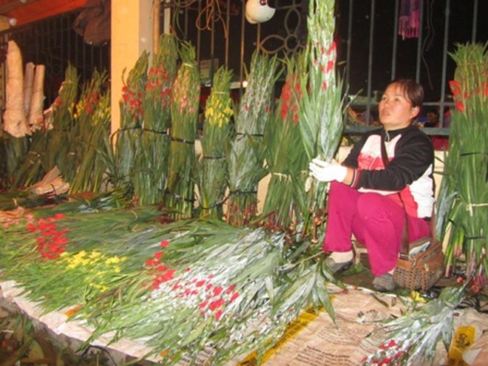 """Cả quầy hoa lay ơn này đã được bán hết, giờ thì bà chủ chỉ còn việc ngồi chia nhỏ từng chục hoa theo yêu cầu của người mua và trả lời an ủi những khách hàng đến muộn """"Hết mất rồi, hẹn mai nhé!""""."""