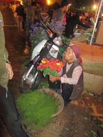 """Bên cạnh những hàng hoa lộng lẫy, tấp nập, bó hoa của bà cụ trông thật nhỏ nhoi như chính bà: """"Mua hoa đi cô, tự tay tôi cắt vườn nhà đấy, tươi lắm!""""."""