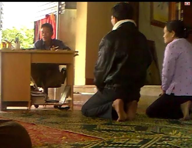 """""""Thánh"""" ngồi chễm chệ trên ghế, để bắt bệnh cho hai người đến khám (ảnh chụp từ video)."""