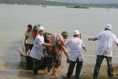 Tiếp cận những người bị nước cuốn trôi đưa lên xuồng để về trạm cấp cứu