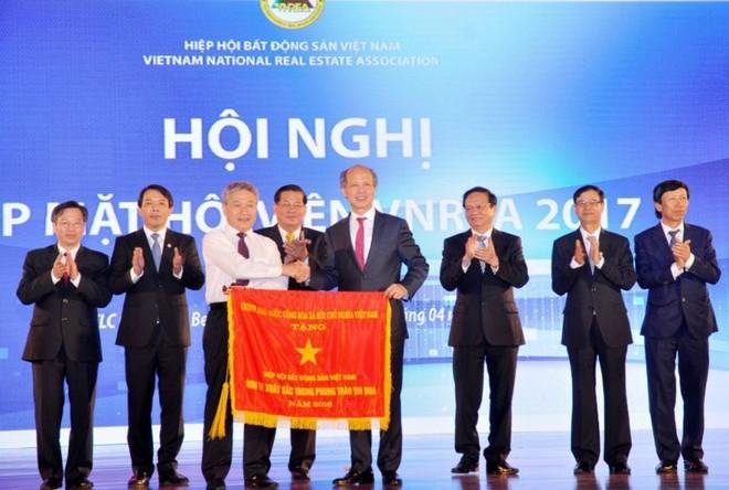 Thứ trưởng Bùi Phạm Khánh trao cờ thi đua của Chính phủ cho Hiệp hội BĐS Việt Nam.