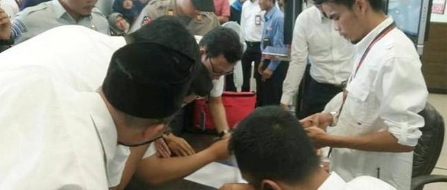 Quan chức Lion Air kiểm tra danh sách hàng khách trên chuyến bay JT610 tại Sân bay Depati Amir. (Ảnh: Reuters)