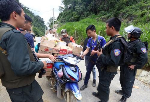 Cảnh sát kiểm tra hàng hoá của người dân trong bản. Ảnh: Bá Đô